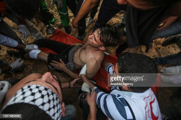Wounded Palestinian Aed Abu Amro who draw interest with his photograph captured by Turkey's Anadolu Agency's photojournalist Mustafa Hassona holding...