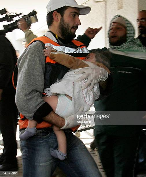 A wounded Palestinian baby is carried into the AlShifa hospital on January 4 2009 in Gaza City Gaza Strip Israeli shells killed at least 12...