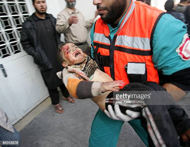 A wounded Palestinian child is carried into the Kamal Adwan hospital after an Israeli air strike on January 11 2009 in Beit Lahia northern Gaza Strip...