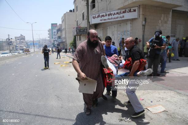 A wounded Palestinian demonstrator carried by people during a protest against Israeli violations and restrictions on Al Aqsa Mosque at Qalandiya...