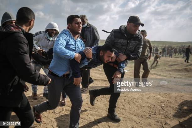 A wounded Palestinian demonstrator is being moved away from the site after the intervention of Israeli security forces during the 'Great March of...