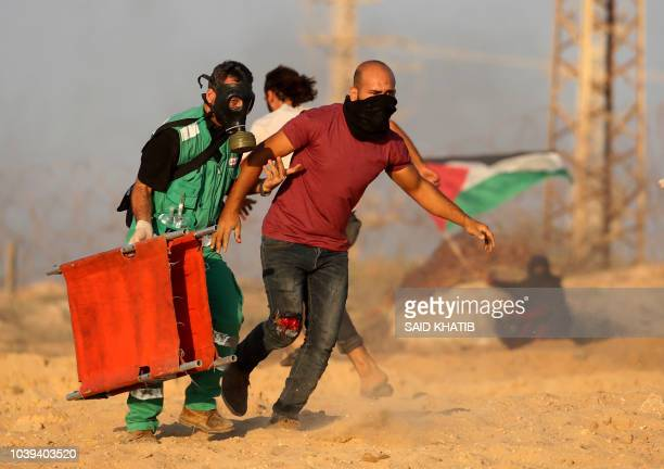 TOPSHOT A wounded Palestinian demonstrator is helped by a paramedic during a protest calling for an end to the Israeli blockade on Gaza on a beach in...