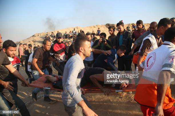 A wounded Palestinian is being carried from the site after Israeli security forces' intervention during a protest organized to mark 70th anniversary...
