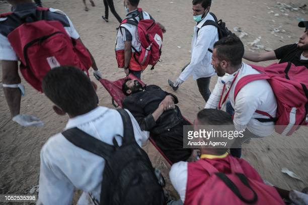 A wounded Palestinian is being evacuated from the site after Israeli soldiers' intervention during the Great March of Return demonstration near...