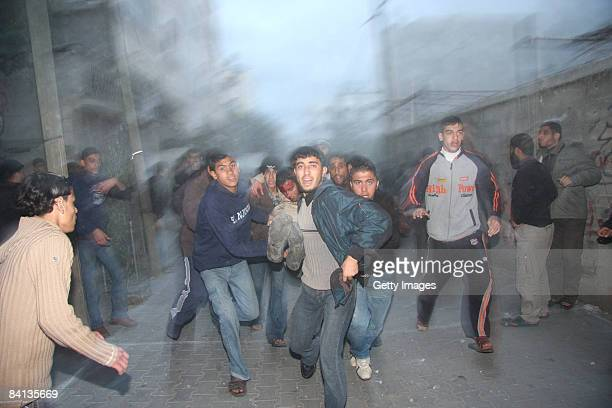A wounded Palestinian man is carried away after an Israeli missile strike on the neighbouring home of a Hamas military leader on December 29 2008 in...