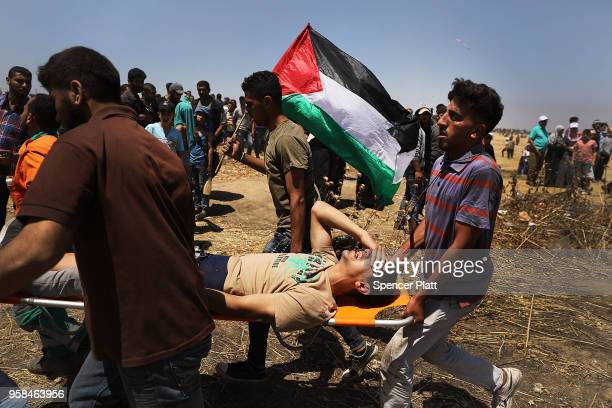 A wounded Palestinian man is rushed to an ambulance at the border fence with Israel as mass demonstrations continue on May 14 2018 in Gaza City Gaza...