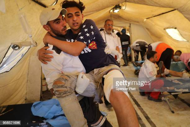 A wounded Palestinian protester arrives at a field hospital near the border fence with Israel as mass demonstrations continue on May 14 2018 in Gaza...