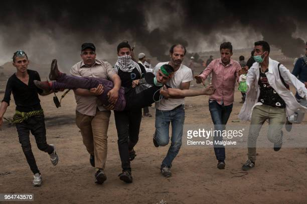 A wounded Palestinian protester is taken away during clashes with Israeli forces on May 4 2018 in Khan Yunis Gaza Israeli troops fired live rounds...