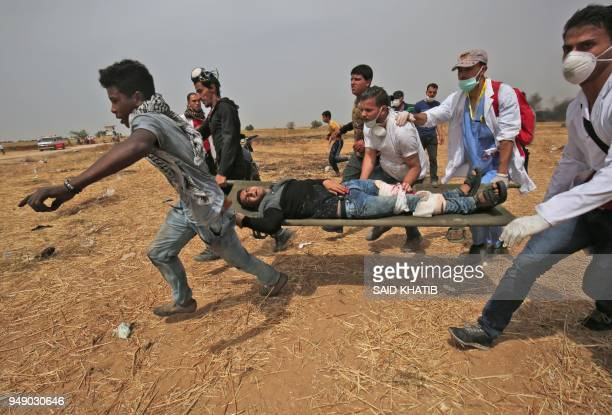 TOPSHOT A wounded Palestinian protestor is evacuated near the border fence with Israel east of Khan Yunis in southern Gaza Strip on April 20 2018...