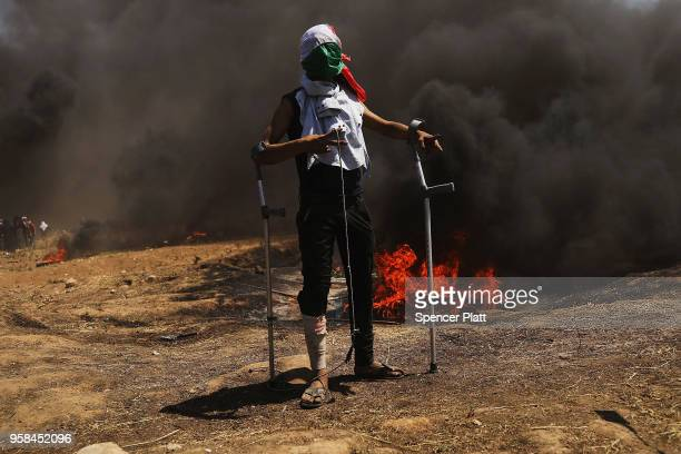 A wounded Palestinian protestor stands at the border fence with Israel as mass demonstrations continue on May 14 2018 in Gaza City Gaza Israeli...
