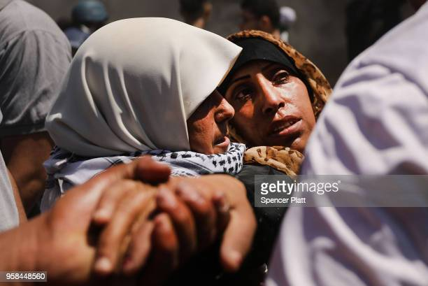 A wounded Palestinian women is carried from the border fence with Israel as mass demonstrations at the fence continue on May 14 2018 in Gaza City...
