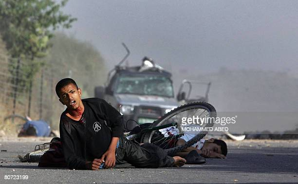 Wounded Palestinian youths lay on the ground near Reuters news agency reporter Fadel Shaana's car after it was hit by an Israeli missile on April 16,...