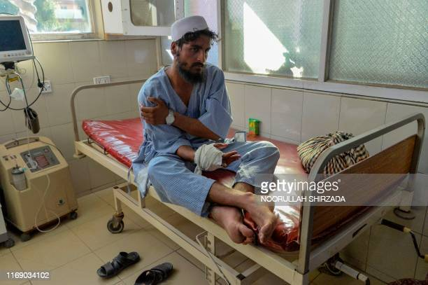 Wounded patients are being treated as they rest on beds at a hospital, following a suicide attack in Jalalabad on September 18, 2019. - At least 12...