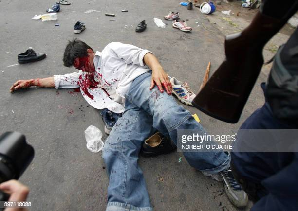 A wounded peasant lies on the street as protesters are repressed by riot police during a demonstration in front of the public prosecutors office in...