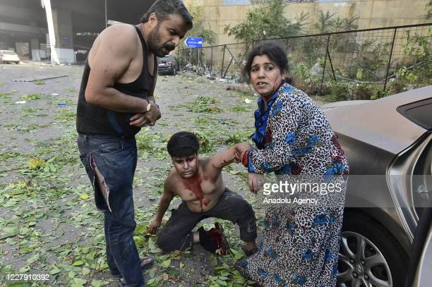 Wounded people are seen near the site after a fire at a warehouse with explosives at the Port of Beirut led to massive blasts in Beirut Lebanon on...
