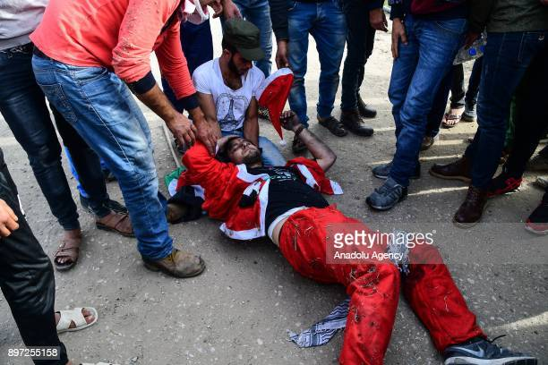A wounded protester dressing up as Santa Clause is seen on the ground after intervention of Israeli security forces during a protest against US...