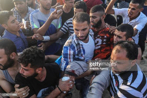 Wounded protester is being carried from the site as Israeli Naval Forces intervene Palestinian demonstrators sailing with 50 boats from Beit Lahia to...