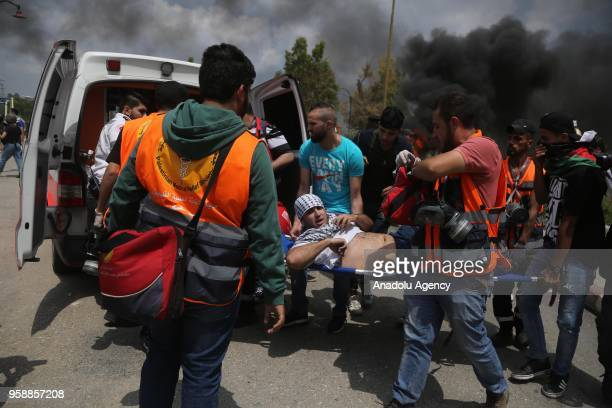 A wounded protester is carried to an ambulance by health team members after being injured on Israeli security forces' intervention during a protest...
