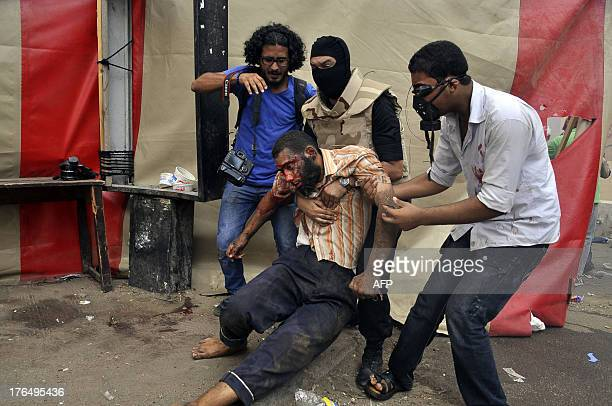 Wounded protester is helped by a fellow supporter of president Mohamed Morsi, a riot policeman and a photographer during clashes that followed an...