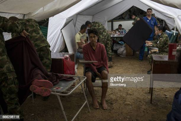A wounded resident sits at a disaster relief center as humanitarian aid workers treat patients after a landslide in Mocoa Putumayo Colombia on Monday...