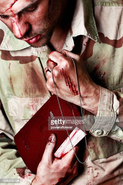 wounded soldier holding bible and gripping dog tags - soldier praying stock photos and pictures