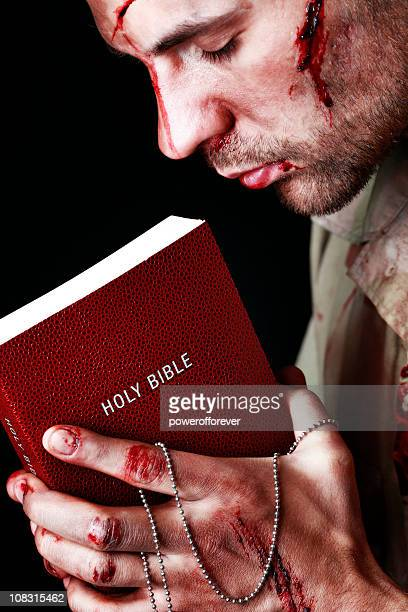 wounded soldier holding bible - soldier praying stock photos and pictures