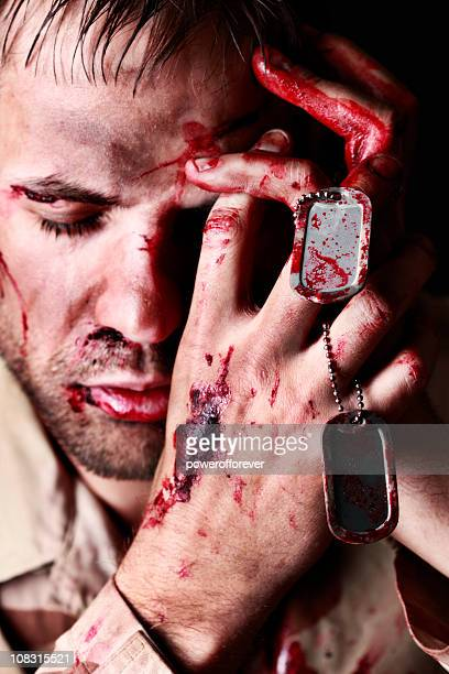 Wounded Soldier Holding Dog Tags in Despair