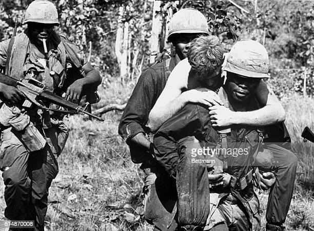 A wounded soldier is carried by members of the 1st Calvary Division while under heavy shelling during Operation Junction City about two miles from...