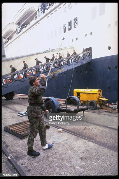 Wounded soldier using crutch to wave goodbye to troops sailing for Falklands on QE2