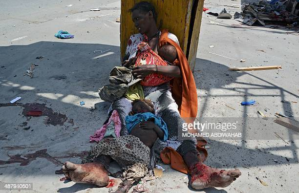 A wounded Somali mother calls for help as she holds her two children one wounded and one dead after a huge explosion believed to be a roadside bomb...