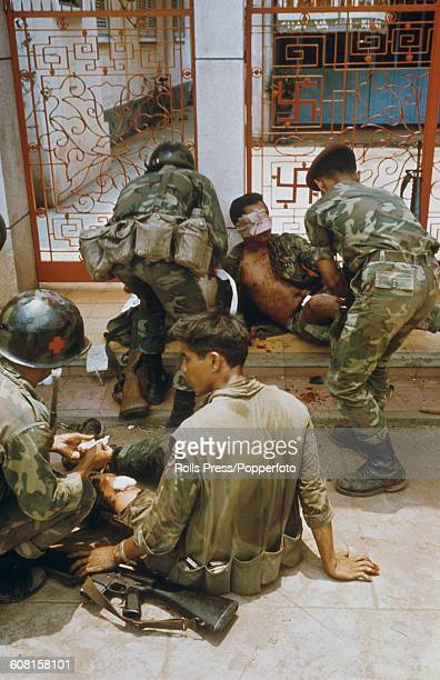 Wounded South Vietnamese ARVN Rangers receive treatment from colleagues in front of a temple during fighting in Saigon between South Vietnamese...