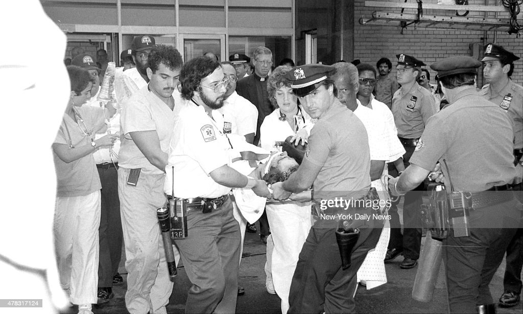 Wounded Steven McDonald is carried from Metropolitan Hospital so that he can be taken to Bellevue. A plainclothes cop was left paralyzed after he was shot in Central Park by one of three junior high school aged boys. McDonald, 29, had his gun leveled on the boys, two age 14, the other 13, about 4:15 p.m. after following them onto a wooded path near Harlem Lake because they 'looked suspicious,' according to police officials. One of the boys pulled a concealed .22-caliber revolver and squeezed off at least four shots at the cop. McDonald collapsed onto the rain-soaked dirt, hit in the neck and right forearm, a bullet lodged against his spinal column. McDonald's partner, Sgt. Peter King, 28, watched the shooting as he ran toward McDonald, who had yelled, 'Hey sarge, I got them down here.' King sprinted to the downed officer, calling for help on a walkie-talkie as he ran. Neither cop fired a shot, according to Richard Condon, first deputy police commissioner.