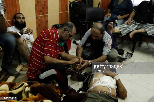 Wounded supporter of deposed Egyptian President Mohammed Morsi is treated by medical staff on the floor of the Rabaa al-Adaweya Medical Centre in the...