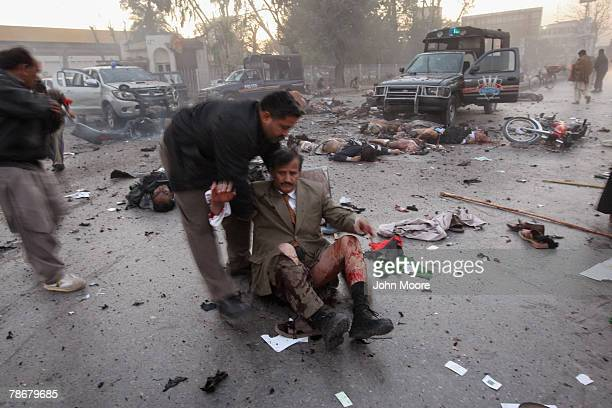 Wounded supporter of former Prime Minister Benazir Bhutto is assisted at the scene of an assassination attack on Bhutto following a campaign rally...