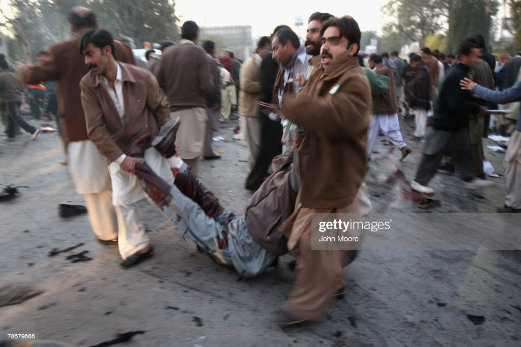 A wounded supporter of former Prime Minister Benazir Bhutto is carried away from the scene of an assassination attack on Bhutto following a campaign rally December 27, 2007 in Rawalpindi, Pakistan. Bhutto was killed as she left the event, while waving to the crowd through the sun roof of her armored car. Dozens of her supporters died in a blast set off by a suicide bomber during the attack.