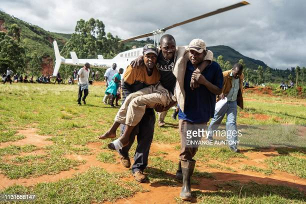 TOPSHOT A wounded survivor is evacuated by helicopter from Chimanimani on March 19 2019 to an hospital in Mutare after the area was hit by the...