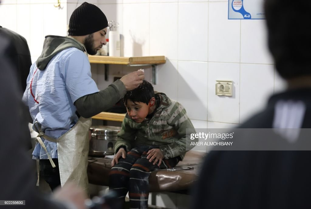 A wounded Syrian boy receives treatment at a make-shift hospital in Kafr Batna in the besieged Eastern Ghouta region on the outskirts of the capital Damascus following Syrian government bombardments on February 21, 2018. Syrian jets carried out more deadly raids on Eastern Ghouta as Western powers and aid agencies voiced alarm over the mounting death toll and spiralling humanitarian catastrophe. PHOTO / Amer ALMOHIBANY