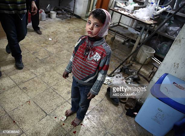 A wounded Syrian child stands at a makeshift hospital in the rebelheld area of Douma east of the capital Damascus as victims of several reported air...
