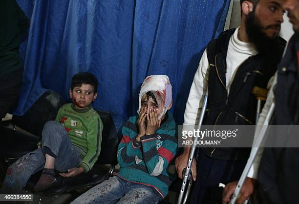Wounded Syrian childrem wait for treatment at a makeshift clinic in the rebelheld area of Douma east of the capital Damascus following reported air...