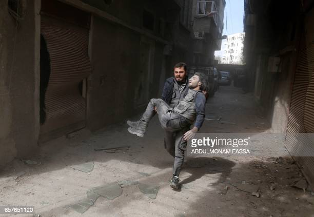 TOPSHOT A wounded Syrian civil defence volunteer also known as the White Helmets evacuates his injured colleague following a reported air strike on...