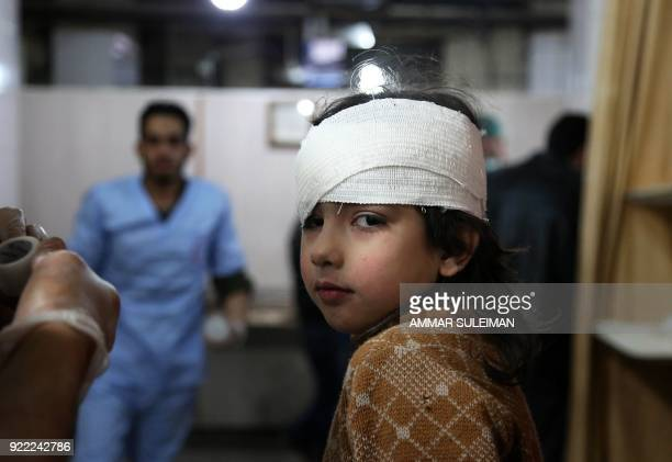 TOPSHOT A wounded Syrian girl receives treatment at a makeshift hospital in Kafr Batna following Syrian government bombardments on the besieged...