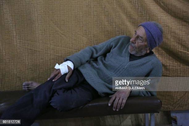 A wounded Syrian man waits to receive treatment at a make shift hospital following government bombardment in Kafr Batna in the rebelheld enclave of...