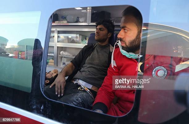 TOPSHOT Wounded Syrian men who were evacuated from rebelheld neighbourhoods in the embattled city of Aleppo sit in a Syrian Arab Red Crescent...