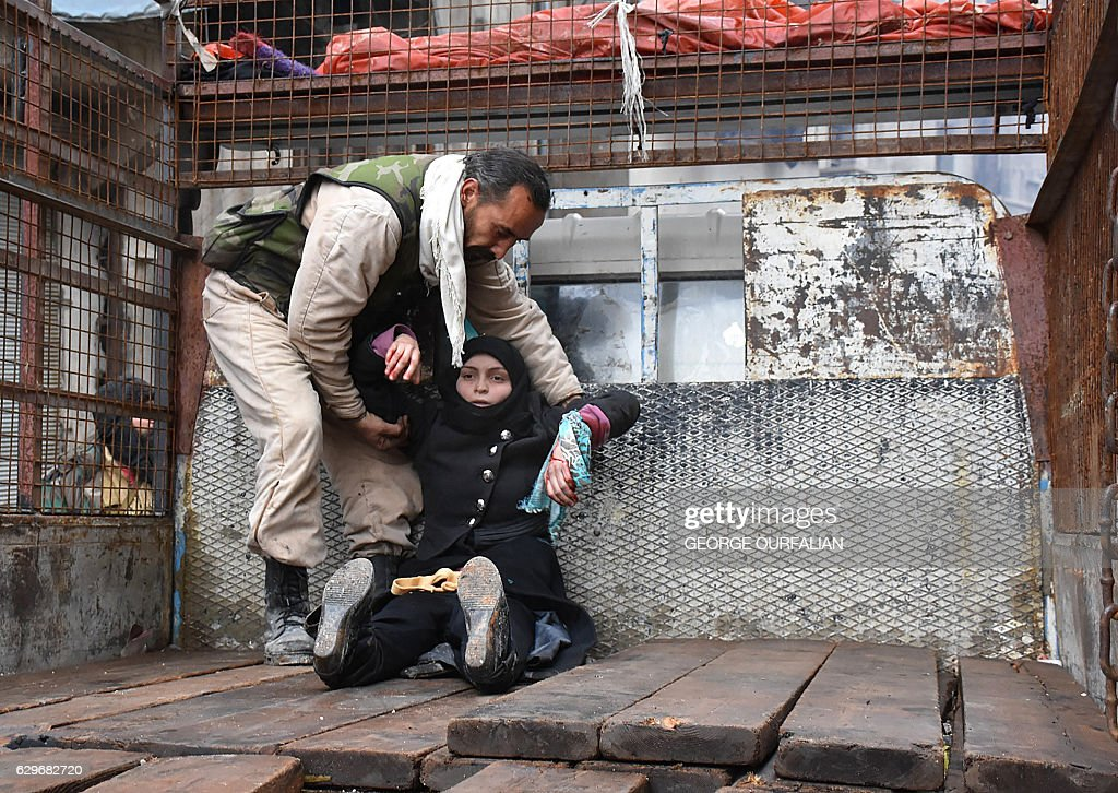 TOPSHOT - A wounded Syrian woman from the al-Sukari neighbourhood is helped onto the back of a truck as she flees during the ongoing government forces military operation to retake remaining rebel-held areas in the northern embattled city of Aleppo on December 14, 2016. Shelling and air strikes sent terrified residents running through the streets of Aleppo as a deal to evacuate rebel districts of the city was in danger of falling apart. / AFP / George OURFALIAN