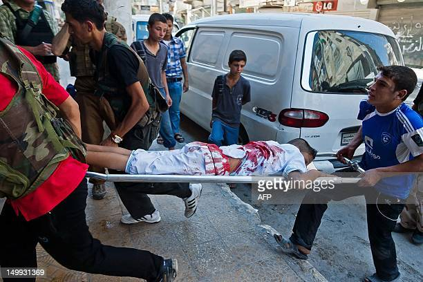 A wounded Syrian youth is carried on a stretcher after he was injured during clashes between rebel fighters and Syrian government forces in the...