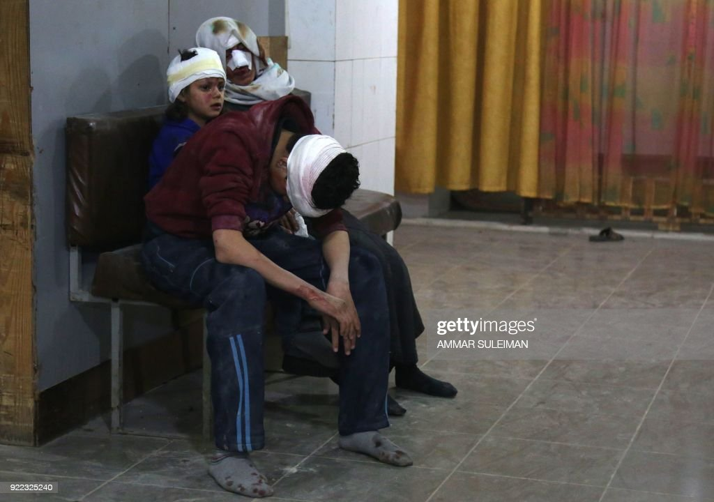 TOPSHOT - Wounded Syrians wait to receive treatment at a make-shift hospital in Kafr Batna following Syrian government bombardments on the besieged Eastern Ghouta region on the outskirts of the capital Damascus on February 21, 2018. Syrian jets carried out more deadly raids on Eastern Ghouta as Western powers and aid agencies voiced alarm over the mounting death toll and spiralling humanitarian catastrophe. PHOTO / Ammar SULEIMAN