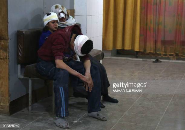 TOPSHOT Wounded Syrians wait to receive treatment at a makeshift hospital in Kafr Batna following Syrian government bombardments on the besieged...