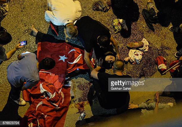 A wounded Turkish woman lies on the ground July 16 2016 in Ankara Turkey Istanbul's bridges across the Bosphorus the strait separating the European...