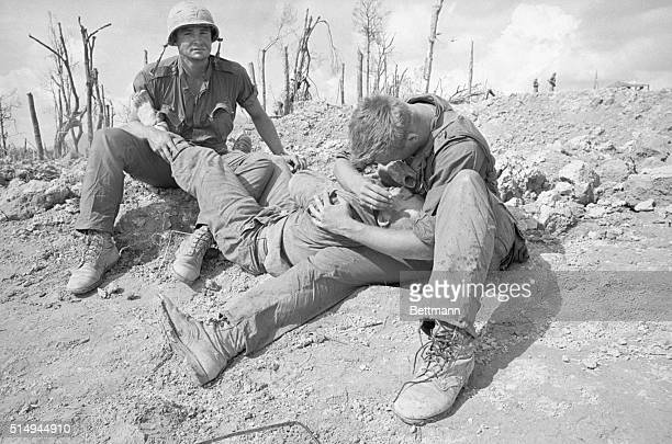 A wounded United States Marine is held in the arms of soldiers while awaiting medical attention during fighting of the Vietnam War on Hill 881 on May...