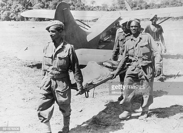 A wounded West African soldier is carried on a stretcher by soldiers after fighting in Burma during the Second World War March 1945